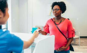 Black woman checking out of doctors office and paying for her bill