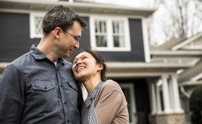 Couple lovingly looking at each other in front of a home that they just purchased