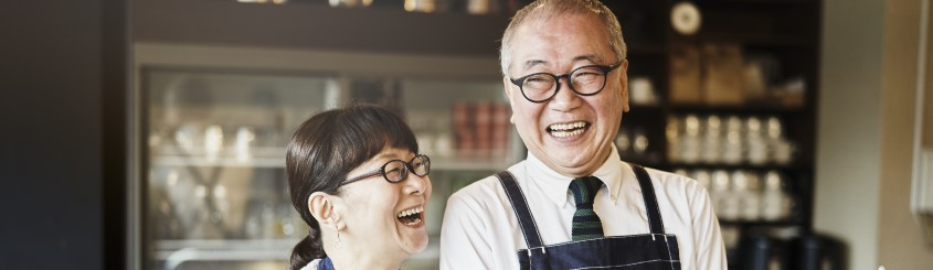 Asian Senior couple who own a cafe smiling and laughing in a cafe large