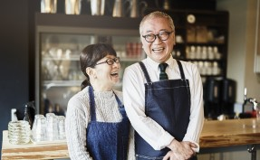 Asian Senior couple who own a cafe smiling and laughing in a cafe