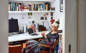 Senior woman sitting in home office using phone small