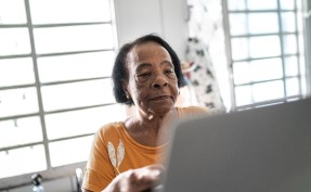Senior woman using a laptop at home sitting in front of bright windows in daylight