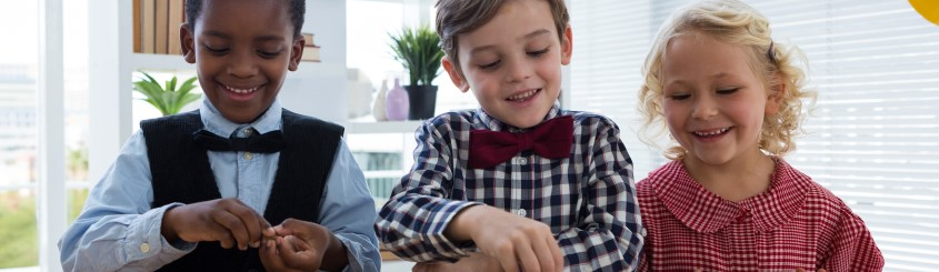 Smiling kids dressed up counting money while standing at table in office large