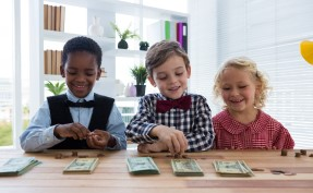 Smiling kids dressed up counting money while standing at table in office