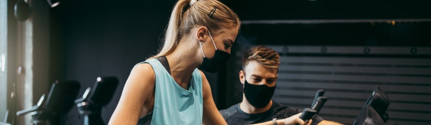Women on an elliptical working out with a male helping to guide her both wearing masks