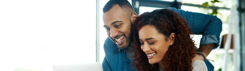 Young couple sitting bin front of a computer smiling