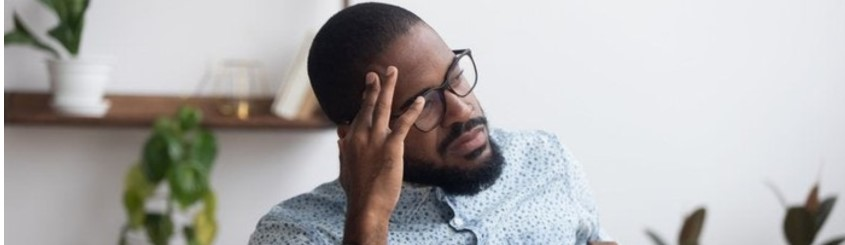 Worried man wearing glasses sitting at the kitchen table with his laptop and hand on his face thinking about finances