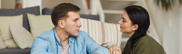 Warm toned portrait of modern young couple talking to each other sincerely while sitting on floor in cozy home interior, cozy space