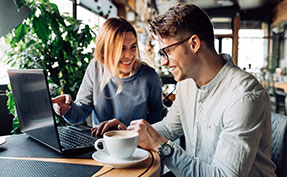 Best friends spending time with pleasure sitting at cafe with laptop