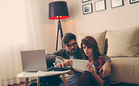 couple reviewing statement in front of computer