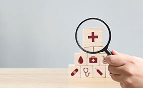 magnifying glass looking at blocks of healthcare symbols