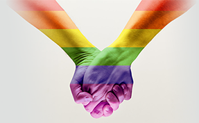 two pride rainbow painted hands holding
