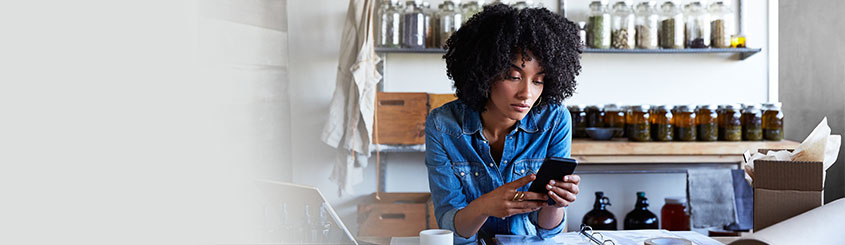 African American Woman reviewing finances on phone