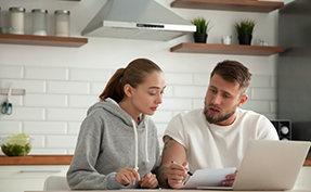 Couple in a kitchen reviewing a statement