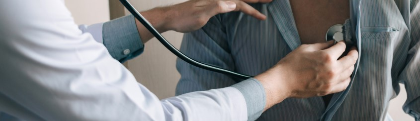 Asian doctor is using a stethoscope listen to the heartbeat of the elderly patient