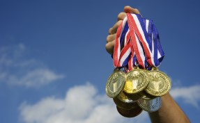 Athlete Hand Holding Up Bunch of Gold Medals Blue Sky