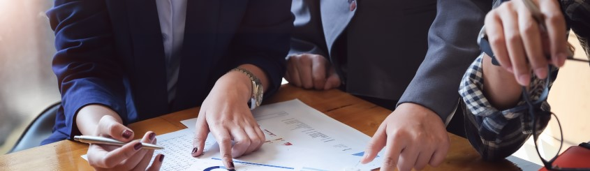 Business people meeting and reviewing paperwork and an analysis at a table