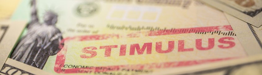 Check with STIMULUS stamped in red, on top of a pile of cash.