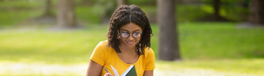 Focused millenial black girl writing something in a notebook in a park