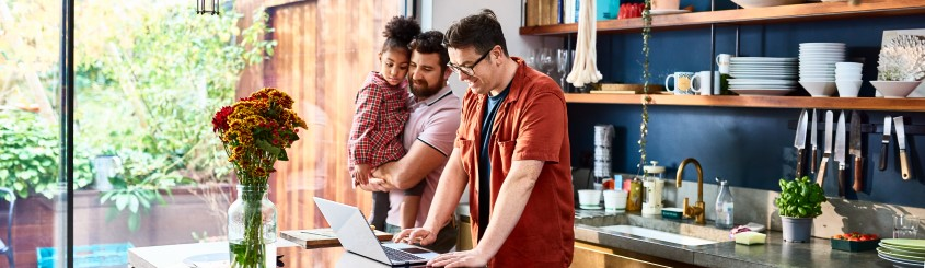 Man working on laptop with husband and daughter in kitchen with a sunny background