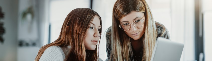 Caucasian mother and daughter looking at a computer with a serious look