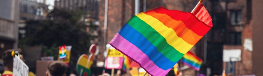 Pride flag at the pride parade waving in the air in a city background