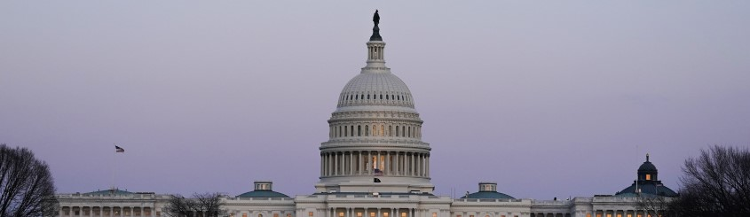 United States Capitol at dusk and a flag flying