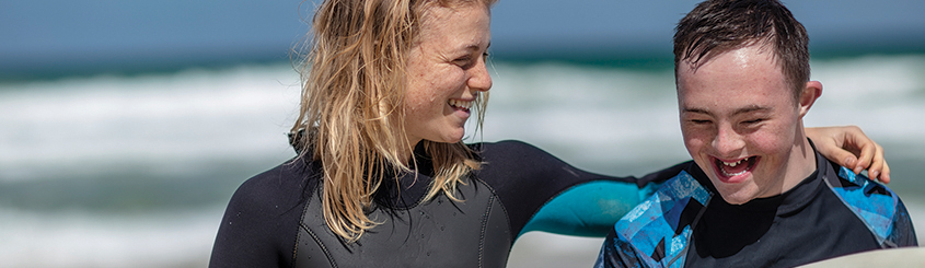Boy with down syndrome surfing with caregiver