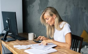 Middle aged woman sitting at a computer looking over her finances