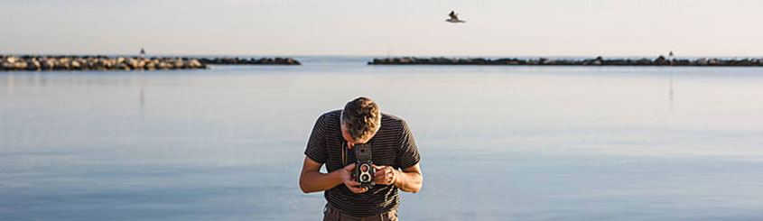 Man looking through view finder taking a photograph